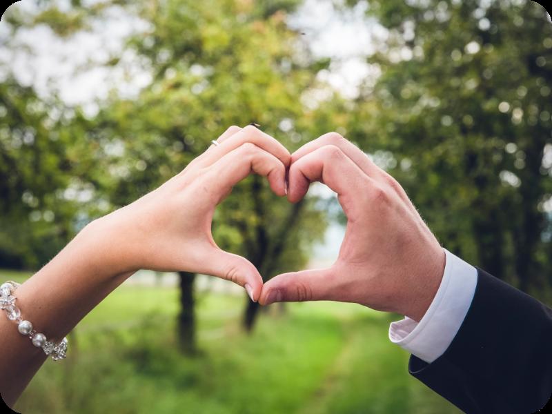 Auf dem Bild sieht man zwei Hände eines Brautpaares bei einer Hochzeit, die ein Herz formen.