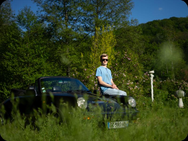 Auf dem Bild sieht man einen alten Porsche und einen Jugendlichen